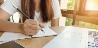 Etudiante travaille à l'écrit devant son ordinateur et son téléphone